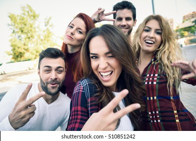 Group of friends taking selfie in urban background. Five young people wearing casual clothes.