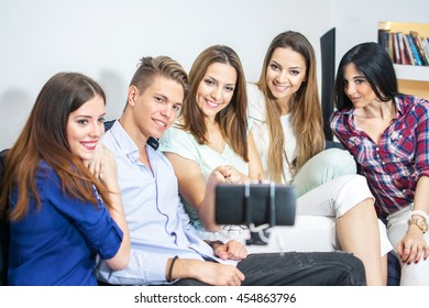 Group of friends taking selfie using selfie stick at home.