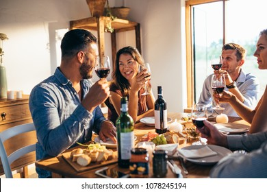 Group of friends talking and drinking sitting at dining table at home. Men and women friends enjoying meal at home together.
