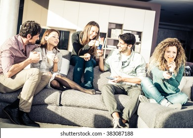 Group of friends talking and having fun while sitting on the couch - Cheerful people meet at friend's home for a coffee break