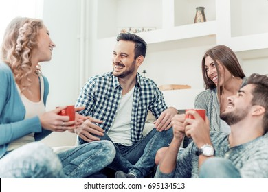 Group of friends talking and having fun while sitting on the couch.They are meet at friend's home for a coffee break.