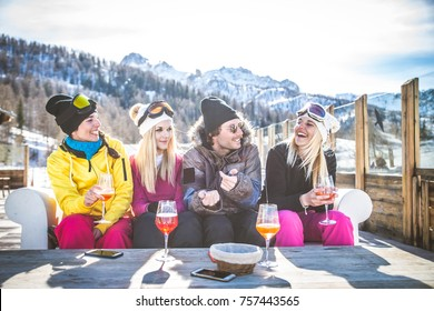 Group of friends talking and having fun in a outdoor restaurant on winter holidays