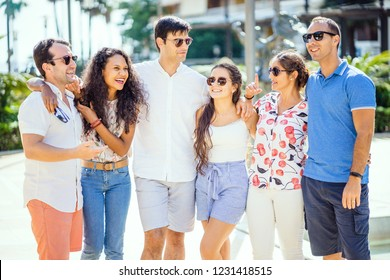 Group of friends talking and laughing during sunny day in the city