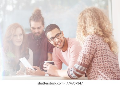 Group of friends talking and laughing during lunch break at the modern office