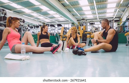 Group of friends talking sitting on the floor of a fitness center after hard training day