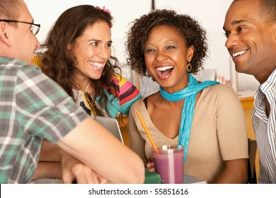 A group of friends are talking and smiling with each other.  One woman is looking towards the camera.  Horizontal shot.