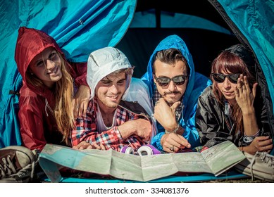 group of friends in a tent watching the map during a rainy day