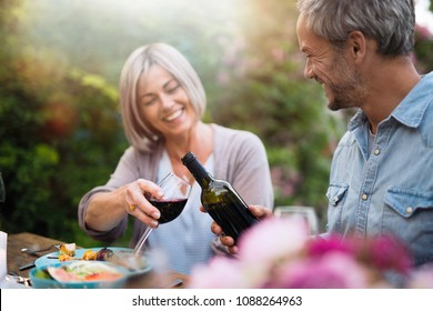 group of friends in their forties gathered around a table in the garden to share a bbq meal. A man offers red wine to a female friend