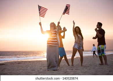 Group of Friends in their twenties dancing on the Beach at Sunset on 4th of July