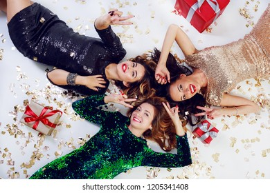 Group of friends , three carefree  elegant successful women  posing on the floor with  shining golden confetti and gift boxes.  Top view.  New year  or birthday celebrating time.