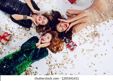 Group of friends , three carefree  women   with surprise faces posing on the floor with  shining golden confetti and gift boxes.  Top view.  New year  or birthday celebrating time. Space for text.