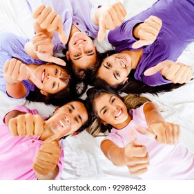 Group of friends with thumbs up lying on the floor