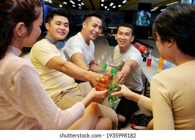 Group of friends toasting with drinks and having fun together during bowling game