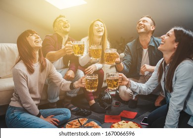 Group of friends toasting with a glass of beer while eating pizza - Millennials have fun together - Day of happiness between young men and women