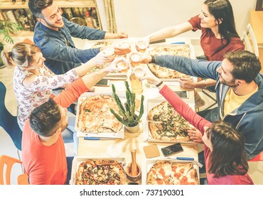 Group of friends toasting glasses of beer while eating pizza in their house - Happy people enjoying dinner together with tasty take away food at home - Concept of friendship, company, lifestyle
