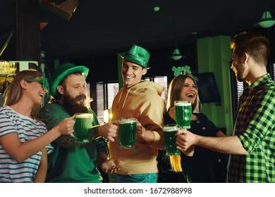 Groupe d'amis grillant de bière verte au pub. Fête de la Saint-Patrick