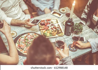 Group of friends toasting red wine in italian winery bar - Young people hands with mobile phones tasting appetizer and drinking together - Focus on right bottom glass  Warm cinematic vintage filter