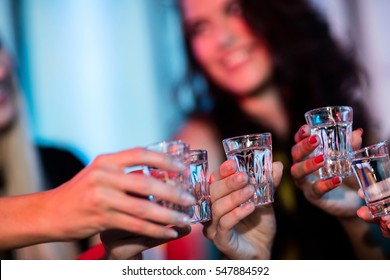 Group of friends toasting tequila shot glasses in bar