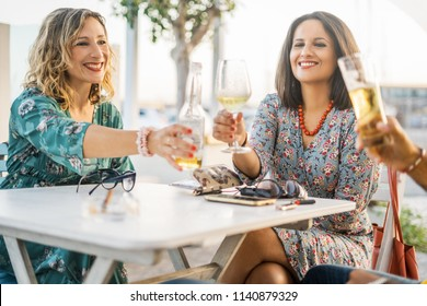 Group of friends toasting wine and beer glasses and having fun outdoors. People eat an aperitif at the bar table