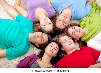 Group of friends together lying on the floor with eyes closed