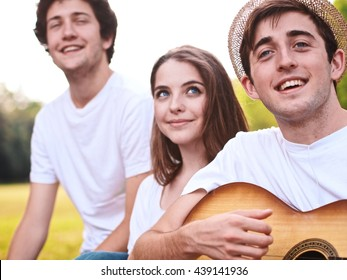 group of friends together in a park having fun and playing music with a guitar