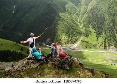 Group of friends or tourists having fun enjoying time together at mountains viewpoint. Travel and tourism concept