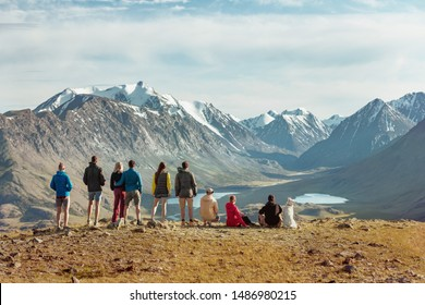 Group of friends or tourists stands on view point in mountains area and having rest