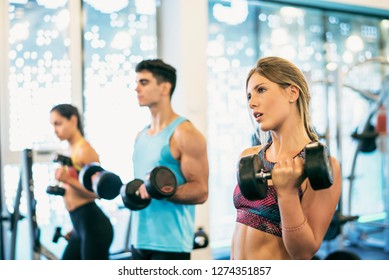Group of friends training with dumbbells biceps exercise in gym