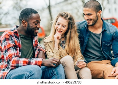 Group of friends two men and one woman with mobile, sitting on a bench in park