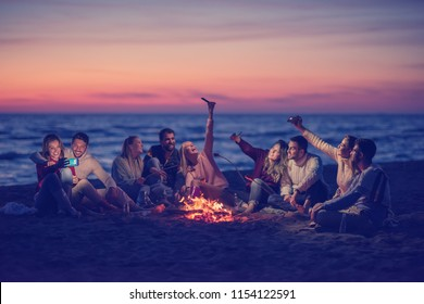 a group of friends using cell phones around the bonfire during autumn beach party drinking beer and having fun