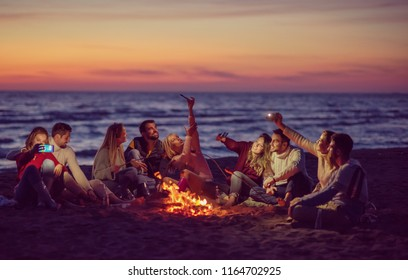 a group of friends using cell phones around the bonfire during autumn beach party drinking beer and having fun filter