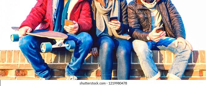 Gruppe von Freunden, die im Winter in Reihe sitzen - Jugendliche, die auf Smartphone SMS schreiben - Jugendliche, die Handy im Freien halten - gepfropftes Bild von Teenagern, die nach moderner Technik süchtig sind