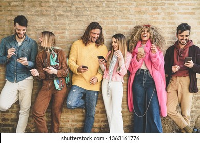 Group of friends using mobile phones outdoor - Young happy people having fun with smartphone apps while smoking cigarettes in the city center - Addiction, tech and youth lifestyle concept