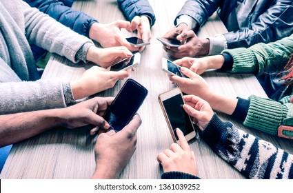 Gruppe von Freunden, die am Sitztisch telefonieren - Multiethnische Menschen, die Smartphone im Kreis halten - Lifestyle-Konzept der neuen Generation und Mobilgeräte-Technologie - Bild