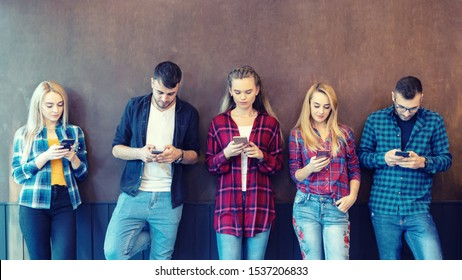 Group of friends using smartphone against wall at university college backyard break – young hipster people addicted by mobile smart phone – technology concept with online connected millennials
