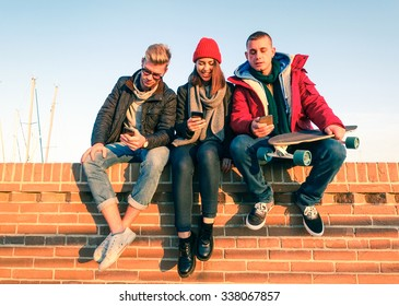 Group of friends using smartphone sitting on low bricks wall - Young people addicted to mobile technology with disinterest talking each other - Teenagers holding telephone outdoor - Concept of leisure