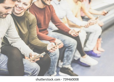 Group of friends using together their mobile smart phones while sitting in underground - Young people surfing on social network on phone - Concept of youth addiction to new technology