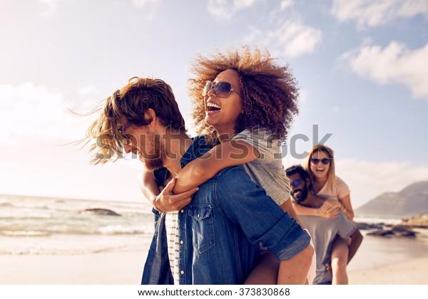 Grupo de amigos caminhando ao longo da praia, com homens dando carona para namoradas. Jovens amigos felizes desfrutando de um dia na praia.