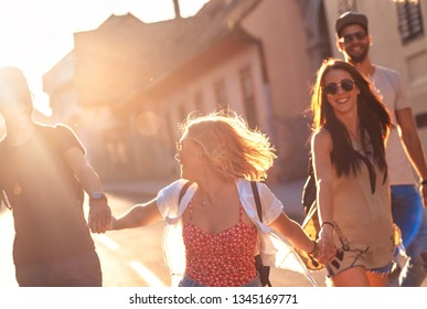 Group of friends walking having fun and laughing at the city street.
