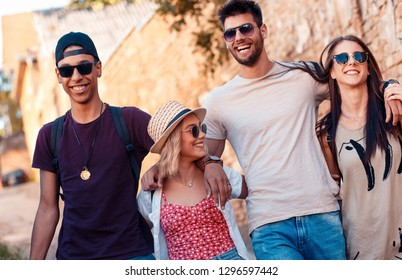Group of friends walking and laughing at the city street.