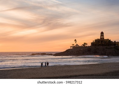 A group of friends walking on Cerritos Beach at sunset.
