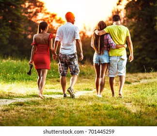 Group of friends walking on the meadow and joying in autumn sunset.