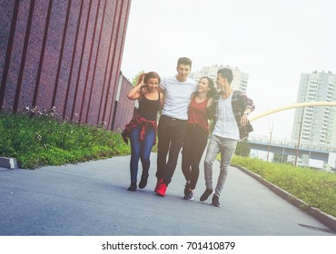 Group of friends walking together outdoor in the city, talking and laughing