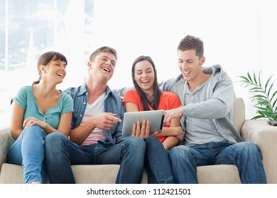 A group of friends watch the tablet pc and laugh as one man points to something on the screen