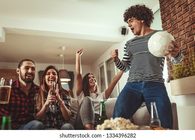 A group of friends watches the broadcast of a sports event. They sit in front of the TV in the living room, eat snack, drink beer, and cheer for the favorite team.