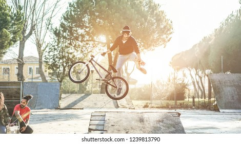 Group of friends watching a biker performing freestyle jump with bmx bicycle - Young people having fun with extreme sport recreation in urban city park - Focus on left man
