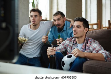 Group of friends watching football match on TV and cheering while sitting on couch and drinking beer