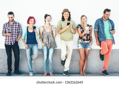 Group of friends watching on their smart mobile phones outdoor - Young generation having fun with new technology and social network - Concept of millennial people, tech and youth lifestyle