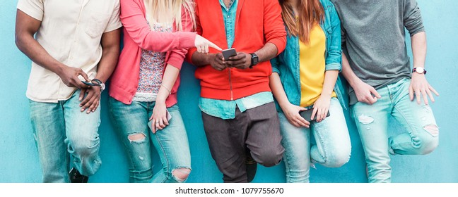 Group of friends watching smart mobile phone - Teenagers addiction to new technology trends - Youth lifestyle, tech, social, millennial generation and friendship concept - Main focus on center hands