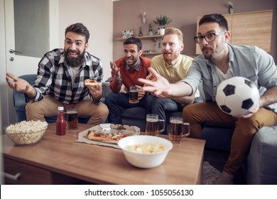 Group of friends watching soccer game on television with beer and pizza.